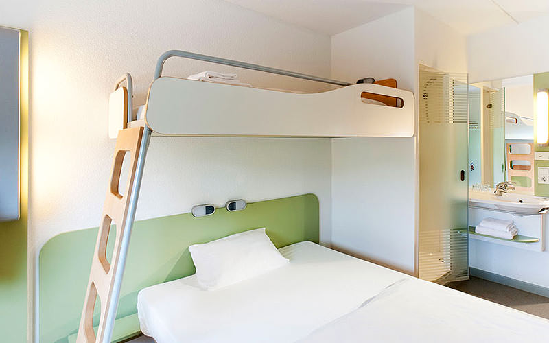 A single bed with a bunk bed over the top, with a pastel green and white colour scheme