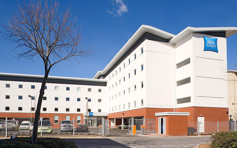 The white and orange exteriors of Ibis Budget Hotel Cardiff, under an extremely blue sky