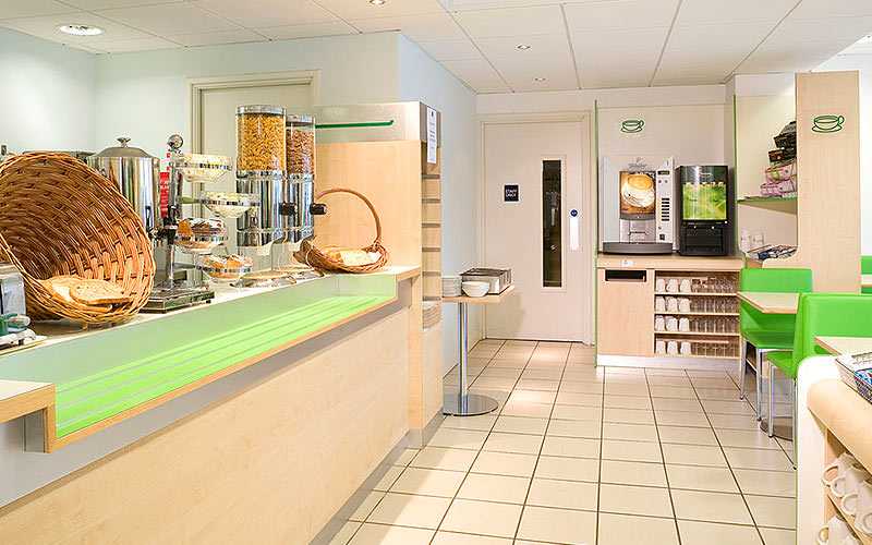 The bright green and cream breakfast bar area of the Ibis Budget Hotel Cardiff