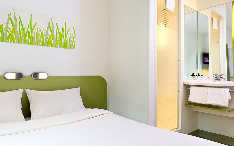 A double bed in a minimalistic room, with a large canvas mounted onto the wall, with grass on it