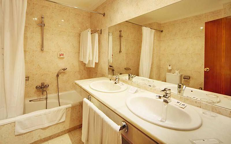 A large bathroom with two sinks, a bath and shower combo and white towels placed on racks throughout