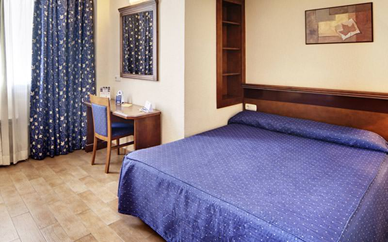 A double room in a hotel with blue curtains and matching bedding