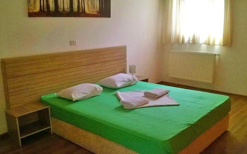 A room with a double bed and a green bedsheet on it