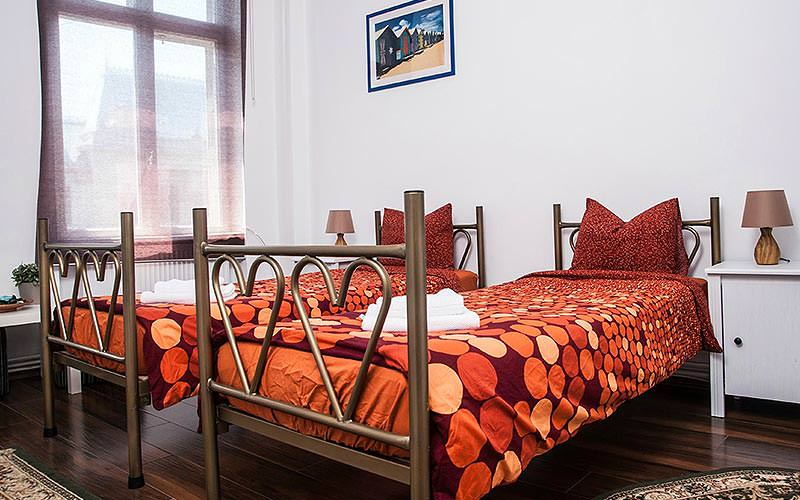 A twin room with orange and red bedding, and a painting mounted on the wall behind