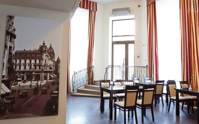 Tables and chairs in a hotel restaurant, with a black and white image of Bucharest on the wall
