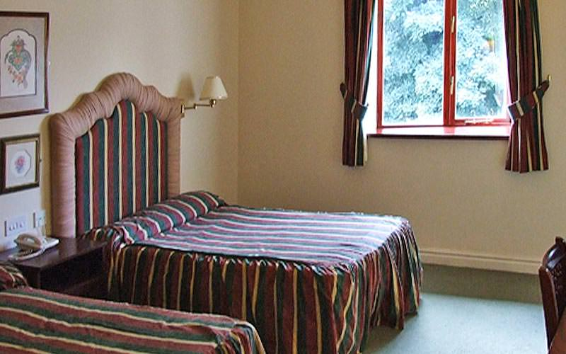 Two beds with striped bedding in a hotel room