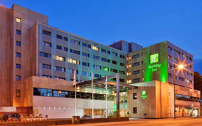 The exterior of Holiday Inn Cardiff City Centre, with the logo illuminated by green lighting