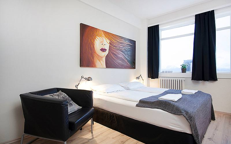 A modern bedroom with a wide painting and a leather chair