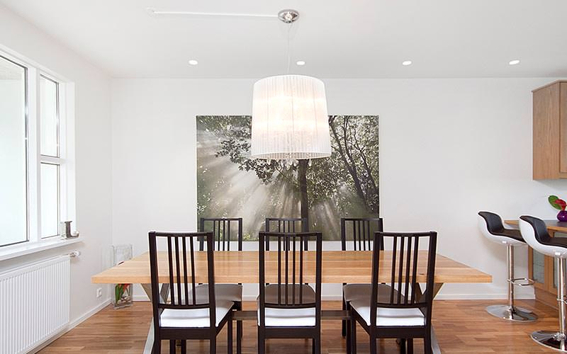 A dining room with a a large photograph on the wall and a wooden dining table and chairs
