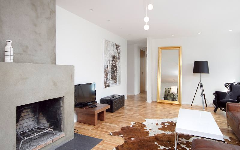 A fireplace and lounge area with a cow-hide rug, ornate wingback chair and tall mirror