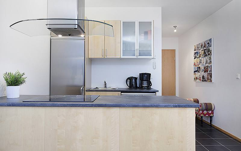 A modern kitchen with induction hob and glass extractor fan hood