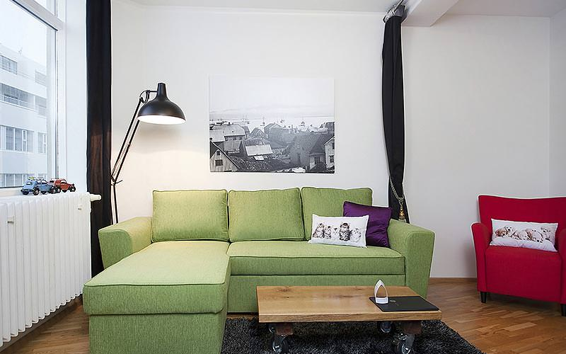 A green corner sofa and wooden coffee table, with an oversized lamp and a small red chair