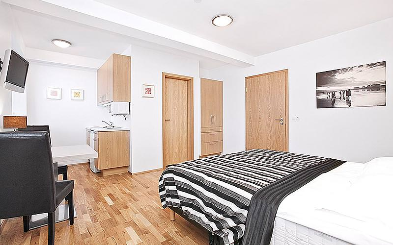 A double bedroom with wooden floors and a flat screen TV