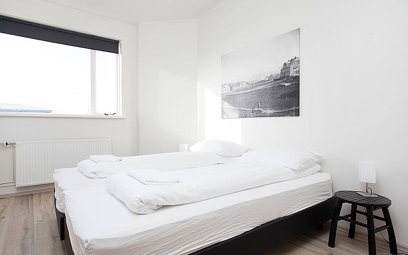 A double bedroom with white linen and a large black and white photograph on the wall