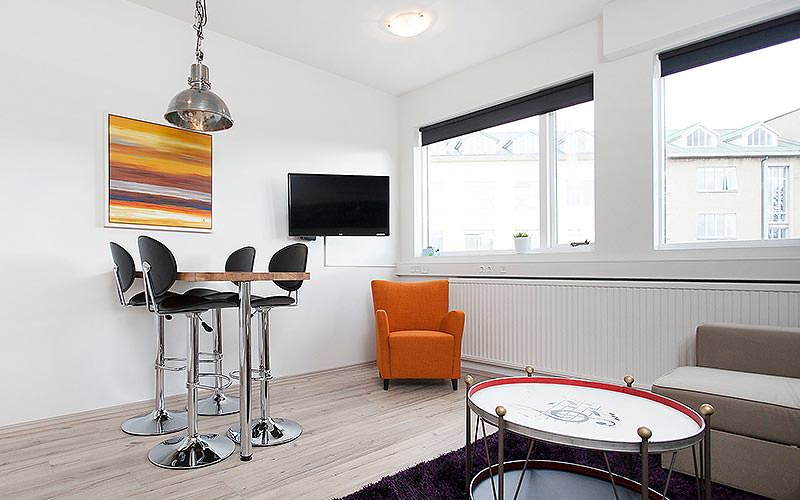 A bright lounge area with a raised dining table, flat screen TV and long radiator