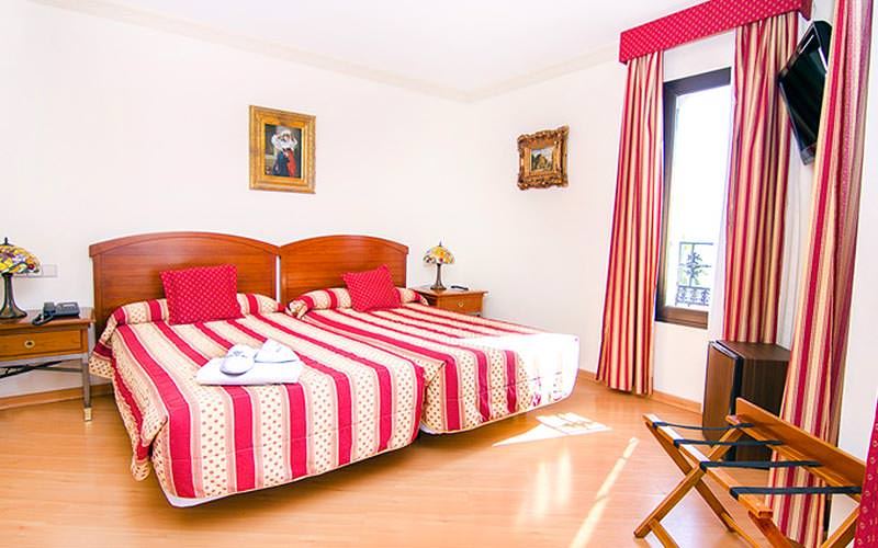 Two single beds in a room with red and white striped bedding and matching curtains