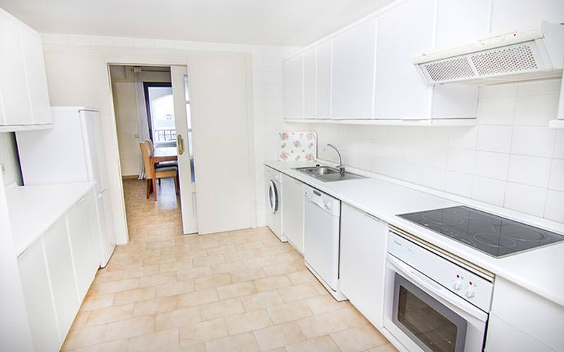 A white kitchenette area with washing machine, cooker and extractor fan