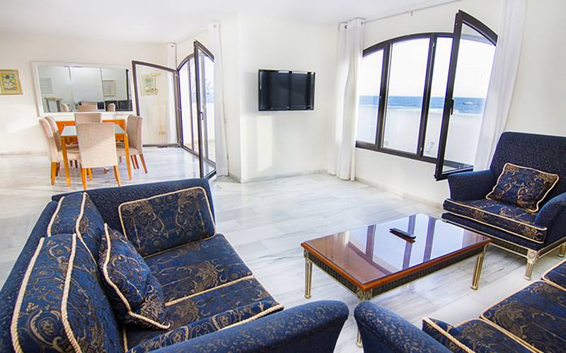 A seating area with navy sofas and a dining table, with two patio windows open, with a sea view visible outside