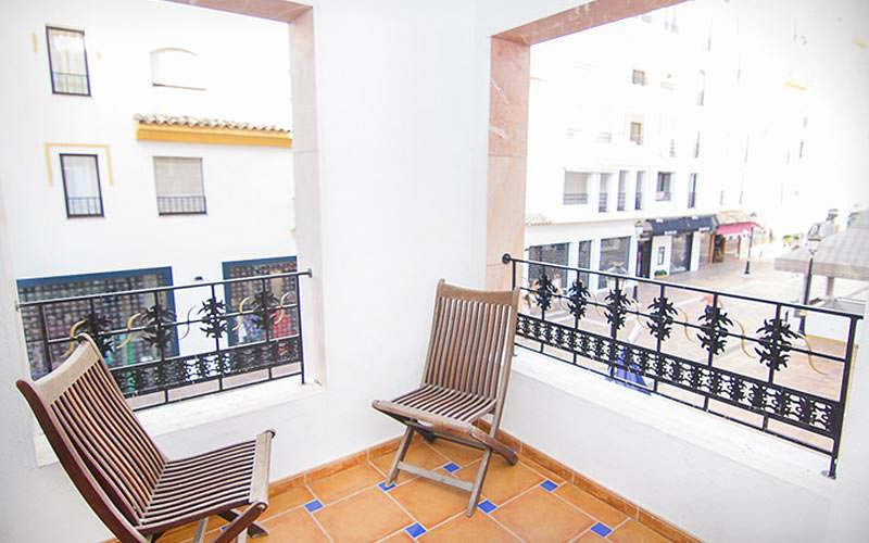 A balcony with two chairs, looking over a street