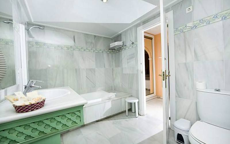 A large, tiled bathroom with a toiler, sink, bath, shower and towel rack
