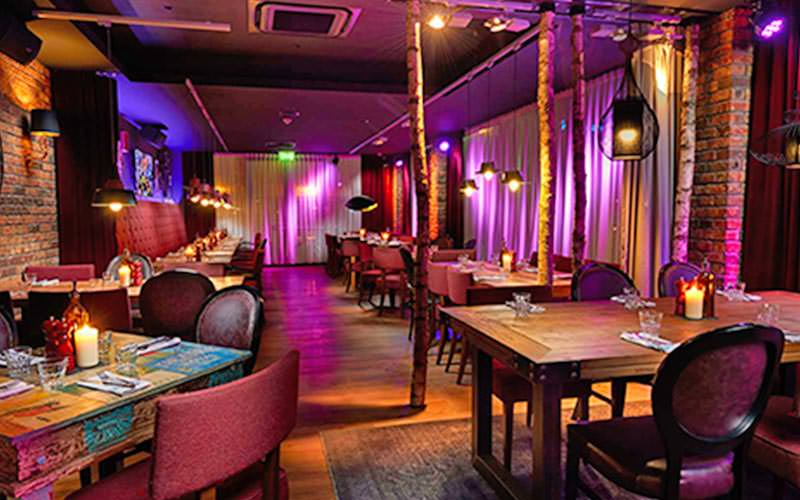 A Hawaiian looking restaurant come bar, with multicoloured lighting and tables set for dinner