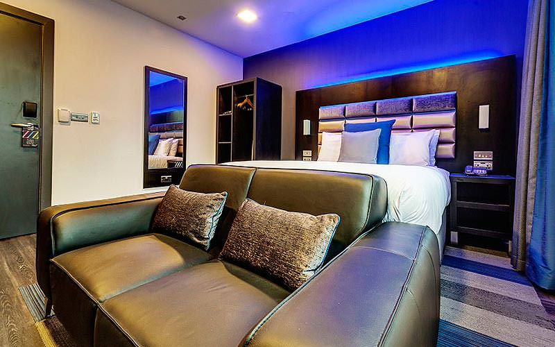 A double bed in a blue-lit hotel room, with wardrobes at the side and a leather sofa at the foot of the bed