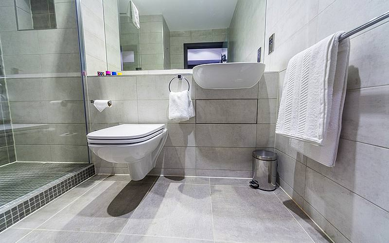 A toilet and sink with a large mirror above, and a glass shower in the corner