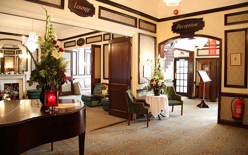 The entrance of the lobby at Redcar Hotel, with seating and a grand piano in the corner, as well as signs for reception and lounge