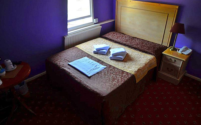 A double bed, with towels folded on top, in the corner of a purple hotel room featuring two tables