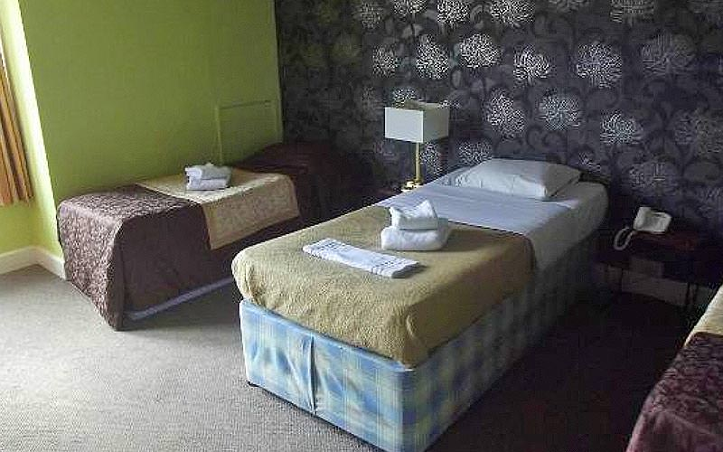 Three singles beds with towels folded up on top, in a green and black hotel room