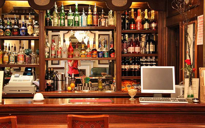 Bottles of spirits stacked on shelves behind a bar, with a computer on the desk in front