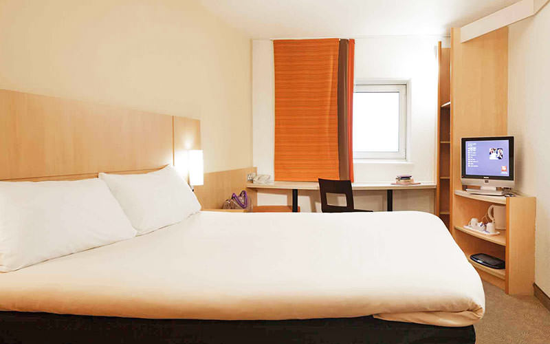 A double bed in a room with a brown and orange curtain, and a small, flatscreen TV on the desk