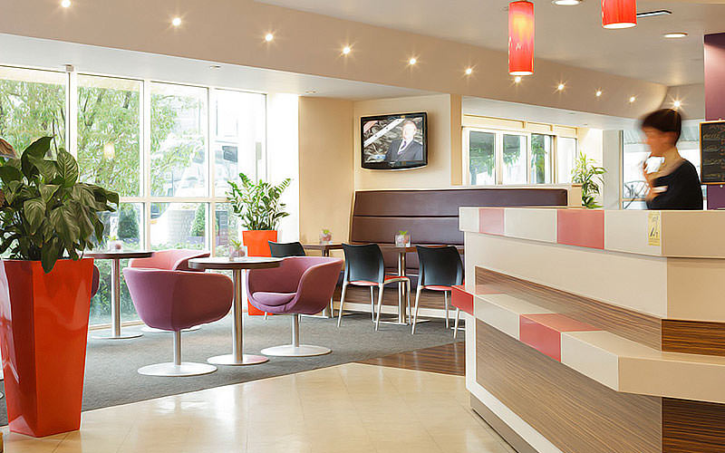 The reception area of Ibis Cardiff City Centre with seating area and receptionist on the desk