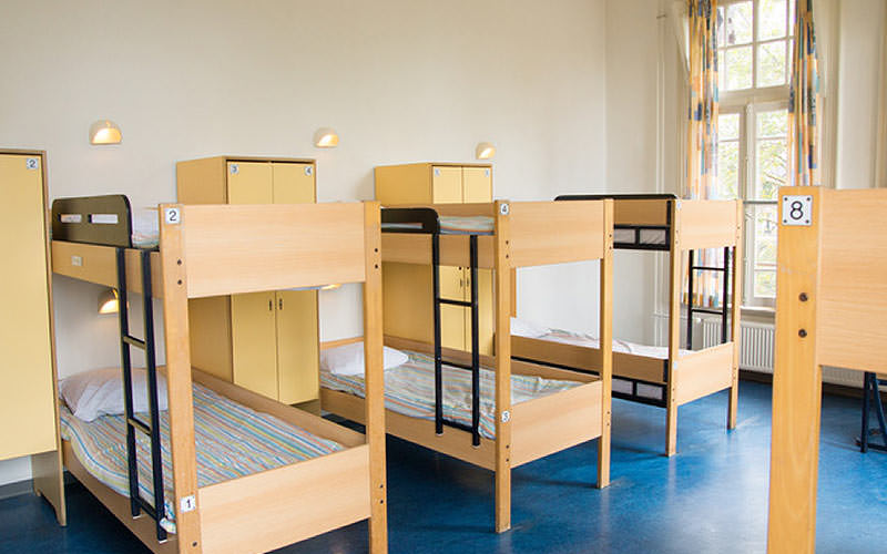 Four wooden bunk beds in a minimalist room