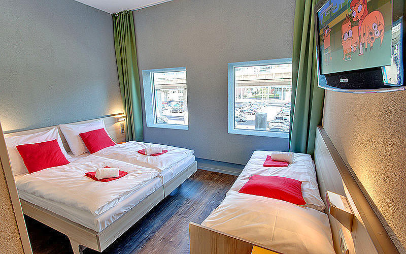 A room with three single beds in, and a flatscreen TV on the wall