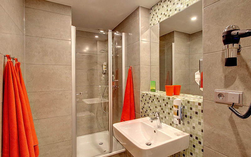 A clean bathroom with red towels hanging and a hairdryer mounted to the wall