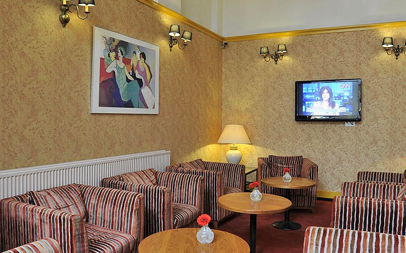 A seating area with striped armchairs and a flatscreen TV mounted on the wall