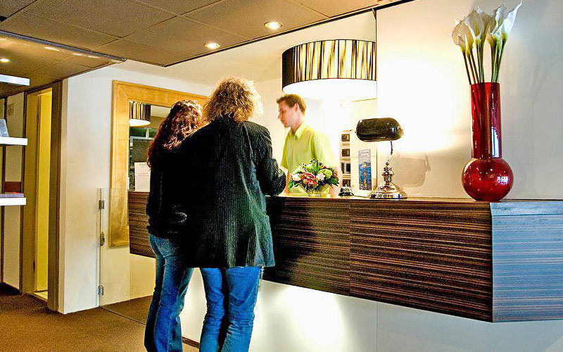 Two people stood at the reception desk and talking to the receptionist at Floris France