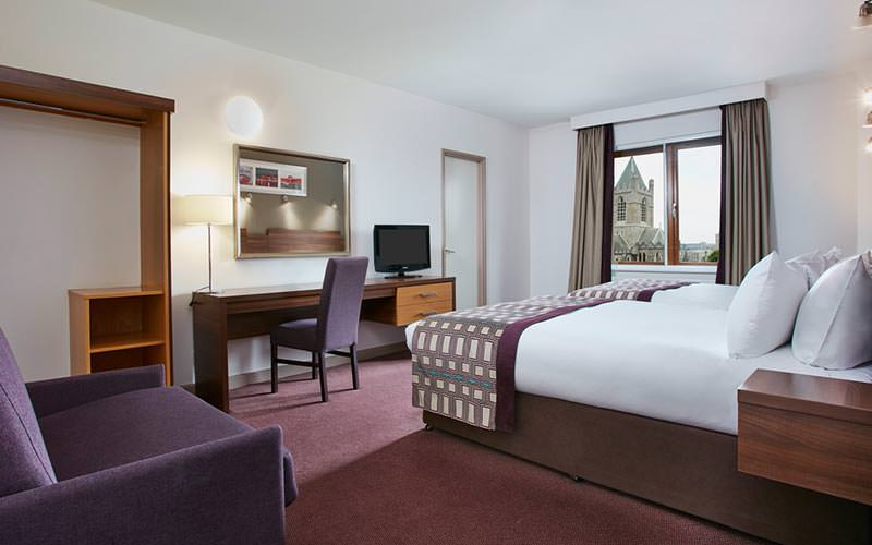 A guest room at the Jurys Inn Christchurch with a double bed, sofa and desk
