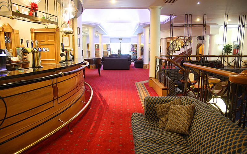 A spacious lobby and bar area with lots of seating and a red carpet