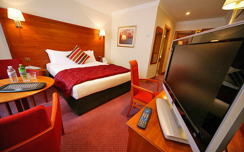 A double room with red interiors and a flatscreen TV in the foreground