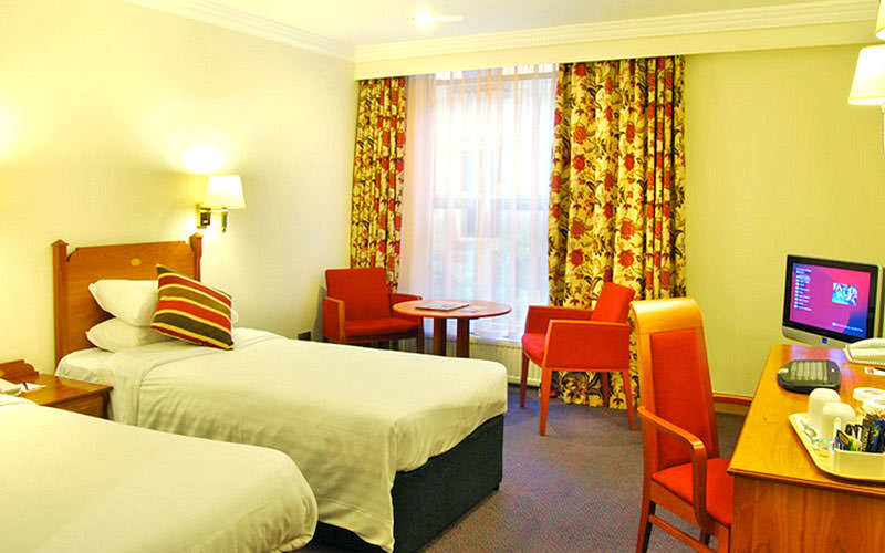 A twin room decorated yellow with a large window and three seats dotted about the room