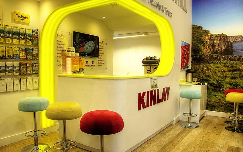 The yellow, lit-up Kinlay Hostel reception, with stools lined in front of the white desk and to the side
