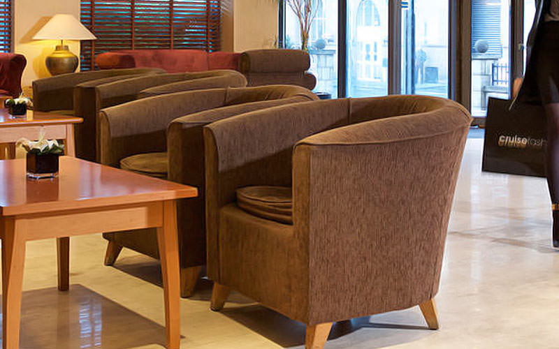The seating area with brown sofa armchairs lined up in the lobby