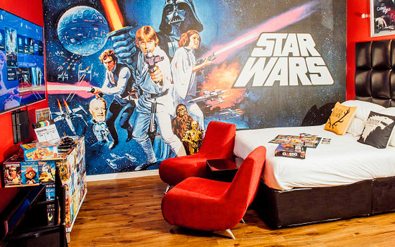 A Star Wars themed hotel room, with Star Wars wallpaper and bedding, and a white double bed facing a desk and two red chairs