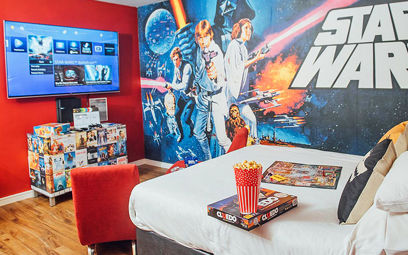 A double bed topped with a board game and popcorn, in a hotel room with Star Wars wallpaper, facing a desk and plasma TV