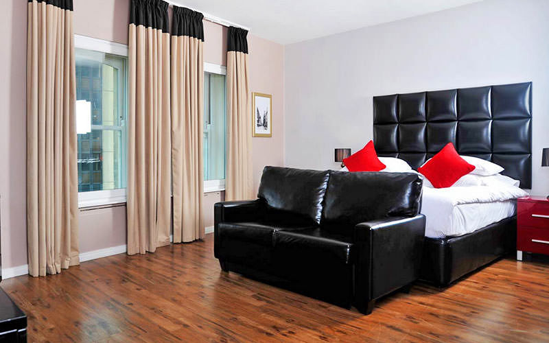 A white double bed with a black leather headboard, in a hotel room, with a black leather sofa at the foot of the bed