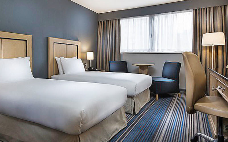 A blue hotel room with two white single beds facing a desk and desk chair, with two blue chairs and a table in the background