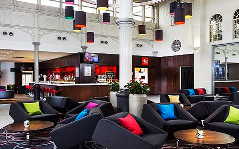 Black chairs with coloured cushions in the hotel lobby of Park Inn by Radisson, Cardiff, with a bar in the background