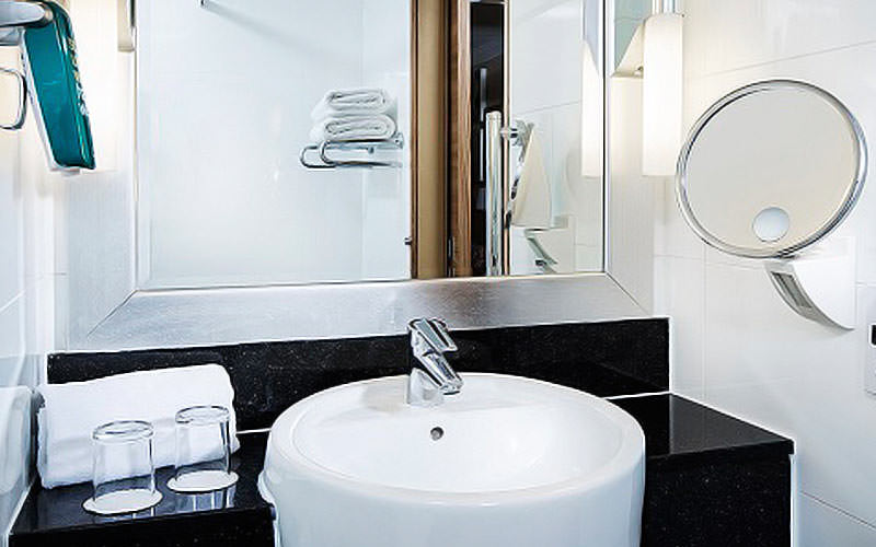 A sink on a black counter, with a mirror, two glasses and a shaver stand on the side of the wall